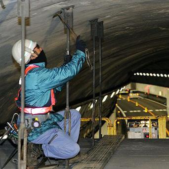 A worker inspects the structure inside the Tsuburano Tunnel on the Tomei expressway in Yamakitamachi, eastern Japan (AP/Kyodo)