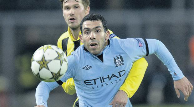 Manchester City's Carlos Tevez tries to hold off Dortmund's Oliver Kirch during their Champions League game in Germany