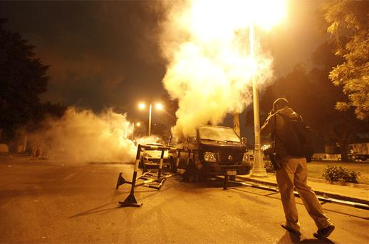An anti-Mursi protester takes a photo of a riot police van with tear gas smoke coming out of it during clashes in front of the presidential palace in Cairo. Photo: Reuters