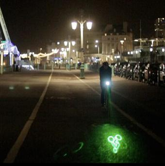 A bike light beams a laser image of a bicycle on to the road ahead to alert motorists (University of Brighton/PA)