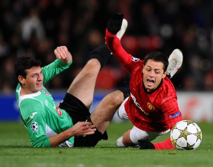 MANCHESTER, ENGLAND - DECEMBER 05: Javier Hernandez of Manchester United is brought down by Ionut Rada of CFR 1907 Cluj during the UEFA Champions League Group H match between Manchester United and CFR 1907 Cluj at Old Trafford on December 5, 2012 in Manchester, England. (Photo by Laurence Griffiths/Getty Images)