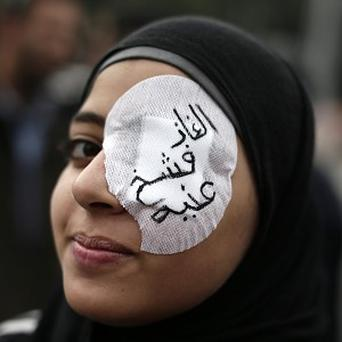 An Egyptian protester wears an eye patch during an anti-Muslim Brotherhood demonstration outside the presidential palace, in Cairo (AP)