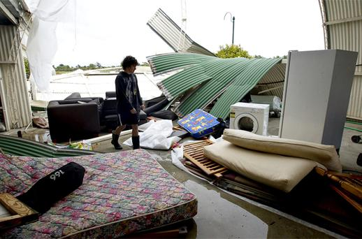 Cale Wood inspects his shed where debris was tossed around in Auckland, New Zealand. Photo: AP