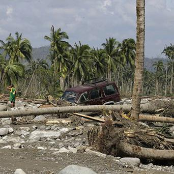 A resident searches for victims of Tuesday's devastating storm in New Bataan township, Compostela Valley in the southern Philippines (AP)