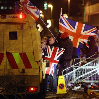 Loyalist protesters carrying Union flags clash with police outside the City Hall in Belfast