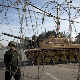 An Egyptian army soldier stands guard next to a tank behind barbed wire securing the perimeter of the presidential palace in Cairo (AP)