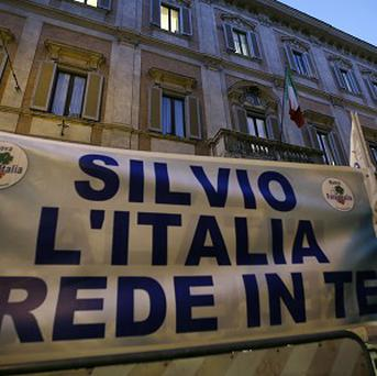 Supporters of Silvio Berlusconi expose a banner reading 'Silvio Italy trusts you' in front of Palazzo Grazioli, his Rome residence (AP)