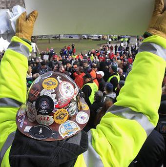 A union steel worker holds up a sign during a rally outside the Capitol in Lansing, Michigan (AP/Carlos Osorio)