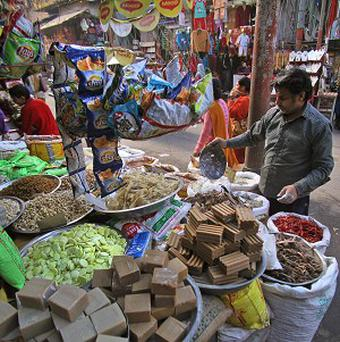 A shopkeeper displays items for sale at a retail grocery store in Jammu, India (AP)