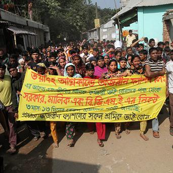 Garments workers shout slogans during a protest outside their factory in Dhaka, Bangladesh, where 112 staff died in a fire (AP)