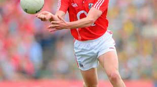 Cork's Patrick Kelly handpasses the ball to a team-mate. The increased use of the handpass is in danger of taking the foot out of Gaelic football.