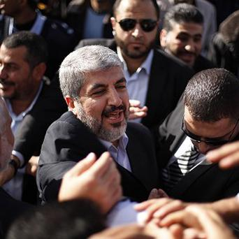 The exiled Hamas chief Khaled Mashaal shakes hands with supporters upon his arrival at Rafah crossing in the southern Gaza Strip (AP)