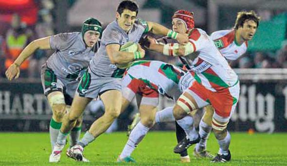 Connacht's Tiernan O'Halloran on the charge against Biarritz's Benoit Guyot.