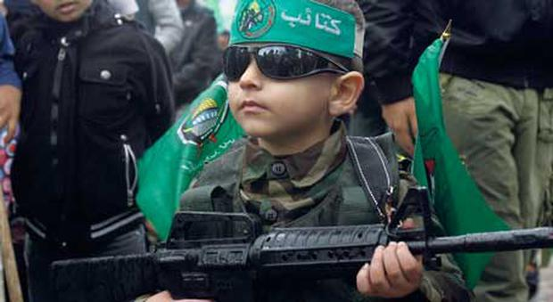 A child, wearing the Islamic green of Hamas, carries a toy gun at yesterday's rally in Gaza City