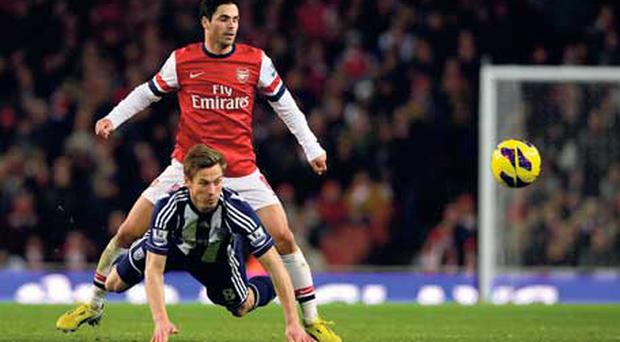 Arsenal's Mikel Arteta challenges West Bromwich Albion's Markus Rosenberg during their Premier League encounter at the Emirates Stadium yesterday.