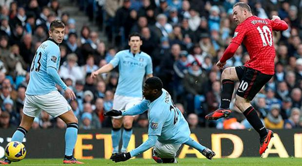 Manchester United's Wayne Rooney (right) scores his teams second goal of the game during the Barclays Premier League match at the Etihad Stadium, Manchester.