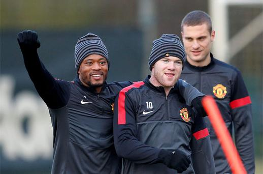 Manchester United's Evra laughs with teammates Rooney and Vidic during training. Photo: Reuters