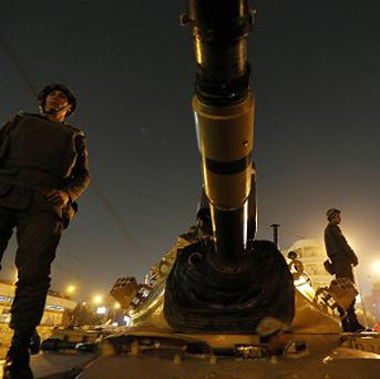 Soldiers stand guard on top of a tank in front of the presidential palace in Cairo (AP)