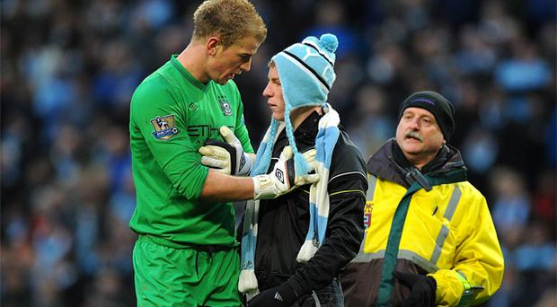 A steward comes to assist as Manchester City goalkeeper Joe Hart (left) holds back a angry fan during the Barclays Premier League match at the Etihad Stadium, Manchester. Photo: PA