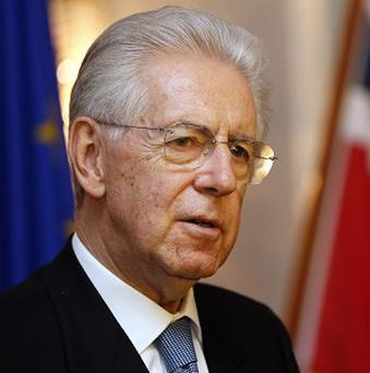 Mario Monti will lead Italy until the next government comes to power, he has said (AP)