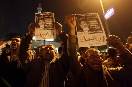 "Supporters of Egyptian President Mohamed Mursi and members of the Muslim Brotherhood chant pro-Mursi slogans during a support rally in Rabaa El Adaweya Mosque square in Cairo, December 9, 2012. Egypt's main opposition coalition rejected Mursi's plan for a constitutional referendum this week, saying it risked dragging the country into ""violent confrontation"".The words on the poster read: ""God with you Mursi, We are proud of you"". REUTERS/Amr Abdallah Dalsh (EGYPT - Tags: POLITICS CIVIL UNREST)"