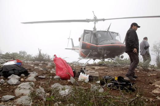 Forensic and criminalistic personnel walk next to a red bag which contains human remains as they inspect the area of the crash site of a plane with Mexican-American singer Jenni Rivera on board, at El Tejocote ranch in the municipality of Iturbide, south of Monterrey, December 10, 2012. Rivera died in a plane crash after the small jet she was travelling in went down in northern Mexico, her father said on Sunday. A spokesman for the state government of Nuevo Leon said investigators had found the remains of Rivera's Learjet, which disappeared from the radar 62 miles (100 km) from the northern city of Monterrey. REUTERS/Daniel Becerril(MEXICO - Tags: DISASTER ENTERTAINMENT)