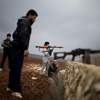 Free Syrian Army fighters take their positions close to a military base (AP)