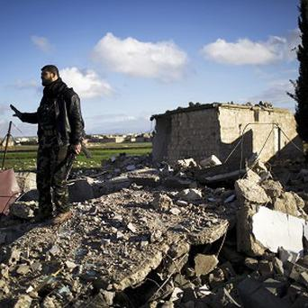 A Free Syrian Army fighter walks over the ruins of a building bombed by a Syrian Army jet in Fafeen village, north of Aleppo province (AP)