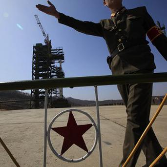 A North Korean soldier stands in front of the country's Unha-3 rocket (AP)