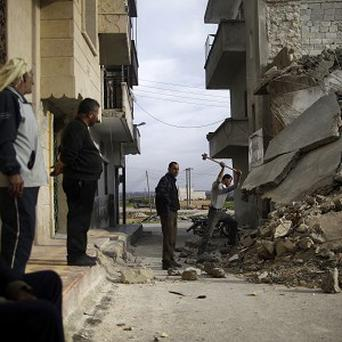 Syrian men use sledgehammers to break the concrete of a residential building destroyed in a government airstrike (AP)