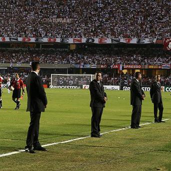Security guards stand guard on the field as Brazil's Sao Paulo FC players and referees wait for the return of Argentina's Tigre's players (AP)
