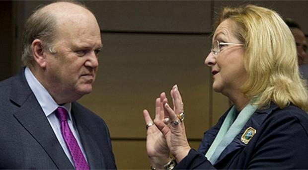 Michael Noonan speaks with his Austrian counterpart Maria Fekter during a meeting of EU finance ministers in Brussels