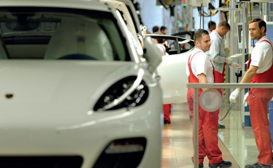 Workers assemble cars at the Porsche factory in Leipzig, Germany