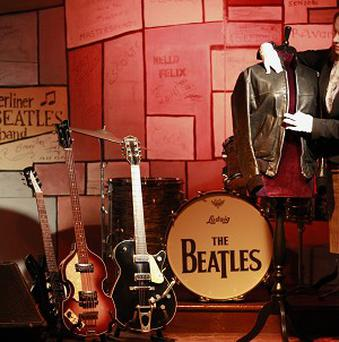 A black leather jacket worn by George Harrison of The Beatles has sold for more than £110,000