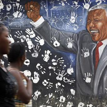 Young women walk past a mural depicting former South African president Nelson Mandela (AP)