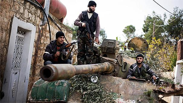 Kurdish members of the FSA are seen on a tank stolen from the Syrian Army in Fafeen village, north of Aleppo province, Syria, Wednesday, Dec 12, 2012