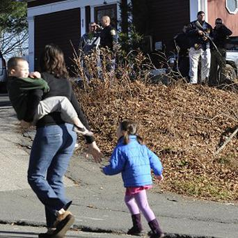 A mother runs with her children as police above canvass homes in the area following the shooting at Sandy Hook Elementary School in Newtown (AP)