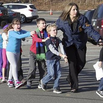 Police lead children from a school following a shooting (AP/Newtown Bee, Shannon Hicks)