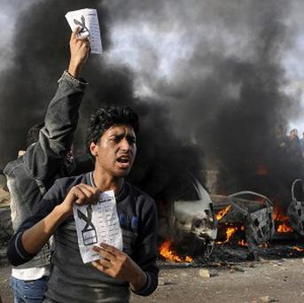 Opponents of President Mohammed Morsi hold pamphlets urging a 'no vote' on a referendum as cars burn during clashes in Alexandria, Egypt (AP)