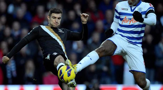 Fulham's Sascha Riether (left) is tackled by QPR's Djibril Cisse. Photo: PA
