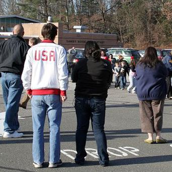 People look on as students are led out of Sandy Hook Elementary School in Newtown (AP)