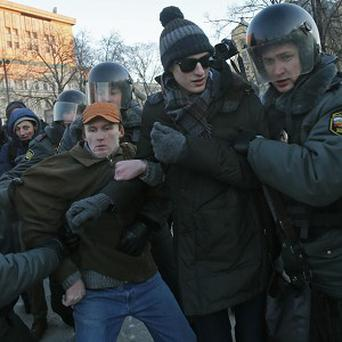 Police officers detain activists during a rally in Moscow (AP)