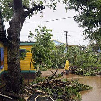 A man wades through deep water in Samoa's capital Apia after cyclone Evan ripped through the South Pacific island nation (AP)