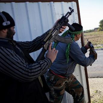 A Free Syrian Army fighter fires his machine gun toward Syrian Army positions (AP)
