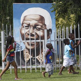 Children pass a portrait of former president Nelson Mandela in a Soweto park (AP)