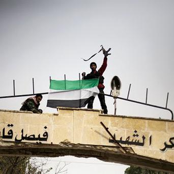 Free Syrian Army fighter puts up a FSA flag after heavy clashes at a military academy besieged by the rebels in Tal Sheer (AP)