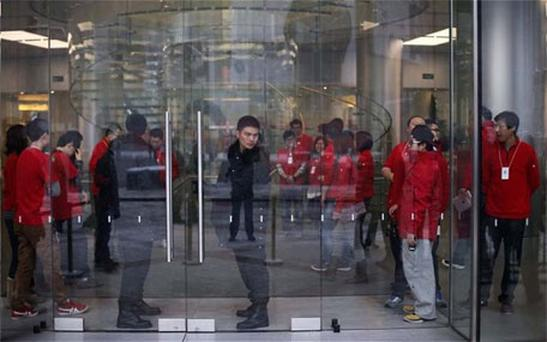 Security guards and staff stand at the entrance of an Apple store during the release of iPhone 5 in Beijing. Photo: Reuters