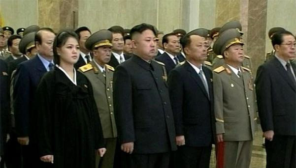 North Korean leader Kim Jong Un, second from left in front row, and his wife Ri Sol Ju, left, attend a ceremony to reopen the mausoleum where his father's embalmed remains will lie in state, as they mark his death one year ago which swept his son to power, Pyongyang. Photo: Reuters