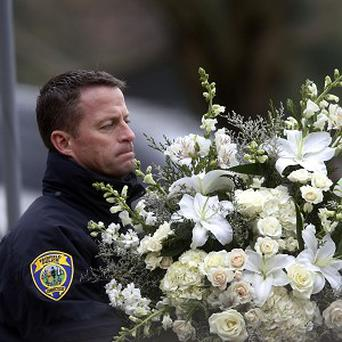 A police officer carries flowers into a funeral service for six-year-old shooting victim Noah Pozner (AP/Jason DeCrow)