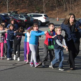 Flashback to police leading frightened children away from the Sandy Hook shooting (AP)